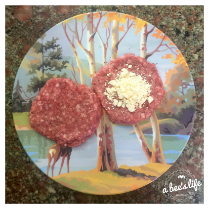 Raw lamb patties with a divot for feta cheese